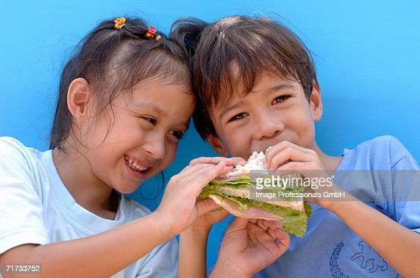 Two children eating a ham sandwich
