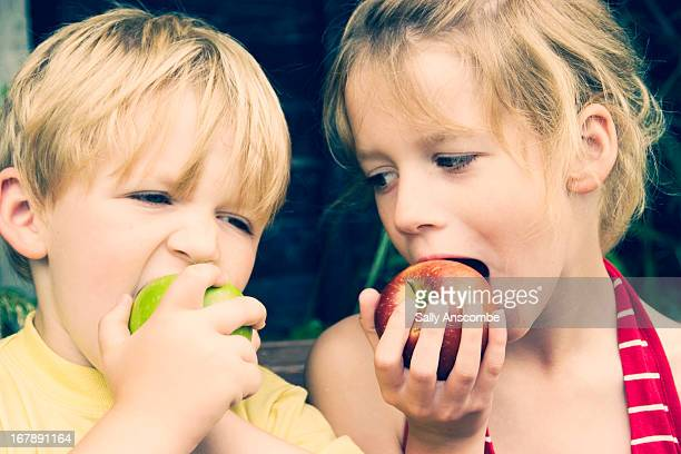 Two children eating apples together