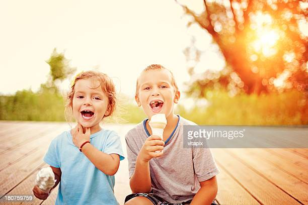 two children eating ice cream cones - girl sitting on boys face stock photos and pictures