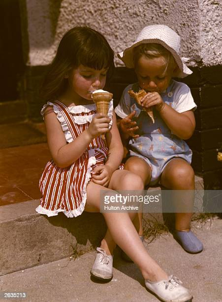 Two children eating ice-creams. The little girl is wearing a pinafore sun dress, and the boy a blue romper suit. Original Publication: Housewife...