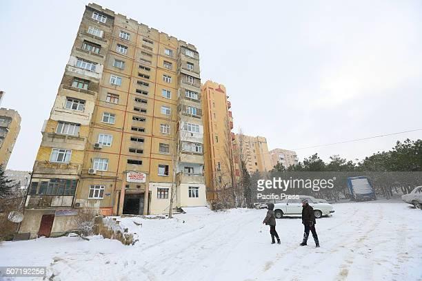 Two children enjoy the snow at the yard in Guneshli district in Baku