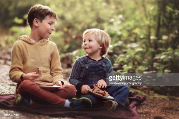 two children enjoying a picnic outside in the forest
