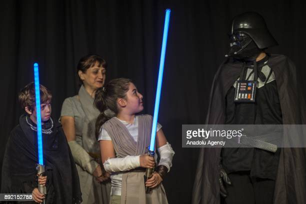 Two children fans with lightsabers stare at another fan dressed up Darth Vader during a gathering for the latest of the Star Wars film series Star...