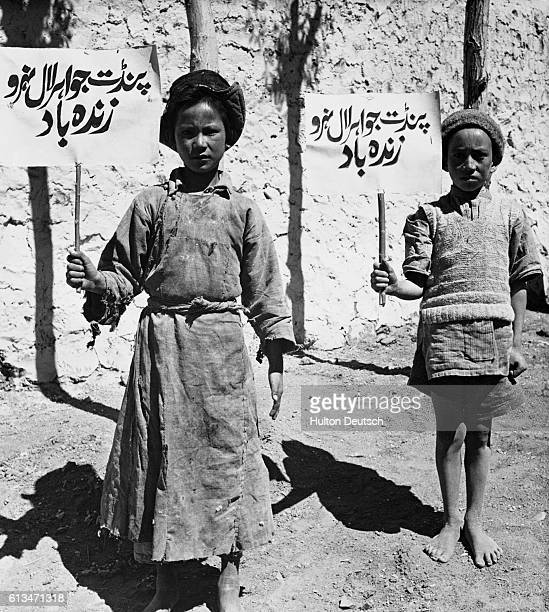 Two children from the disputed Ladakh region carry signs pledging their allegiance to India and Prime Minister Nehru during the 1962 border war...