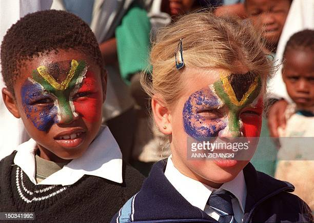 Two children have their faces painted in the colors of the national flag 30 August 1996 in Warrenton north of Capetown where SouthAfrican president...