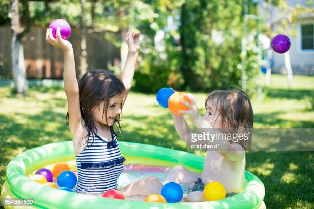 two children having fun in inflatable swimming pool - kids pool games stock pictures, royalty-free photos & images