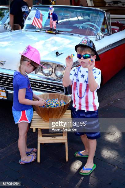 Two children help themselves to free bubble gum at a Fourth of July celebration in Santa Fe New Mexico The boy is asking his mother if he can take...
