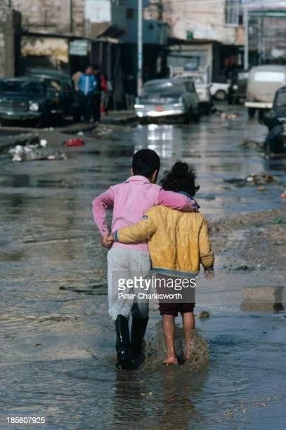 Two children hold each other as they wade through a war torn flooded street in the Shatilla Palestinian refugee camp after heavy rains