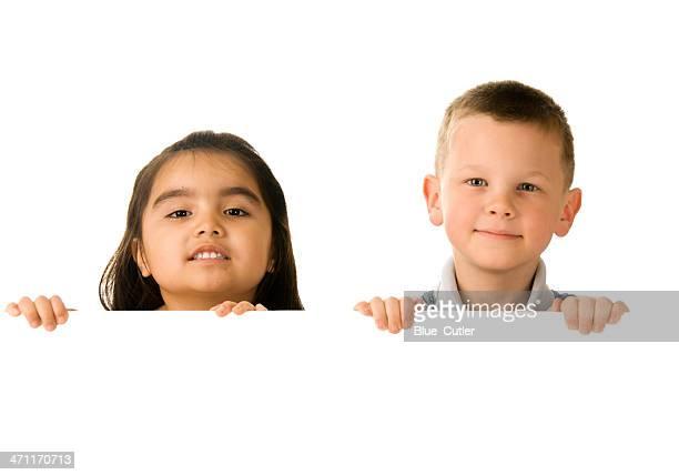 Dos niños sosteniendo un cartel en blanco