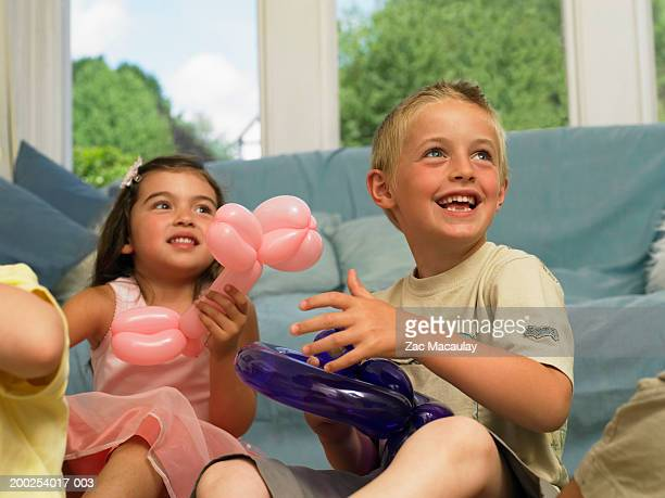 Two children (3-6) holding balloon creations, looking up, smiling