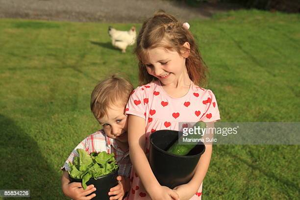 Two children holding organic vegetables