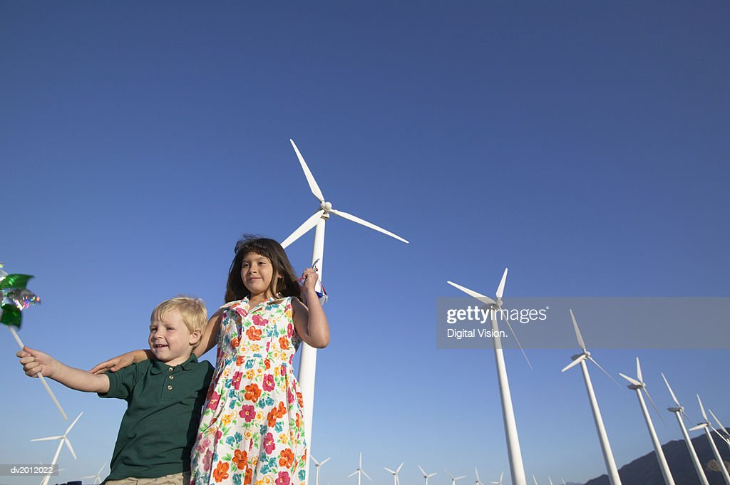 Two Children Holding Pinwheels and Standing in a Wind Farm : Stock Photo