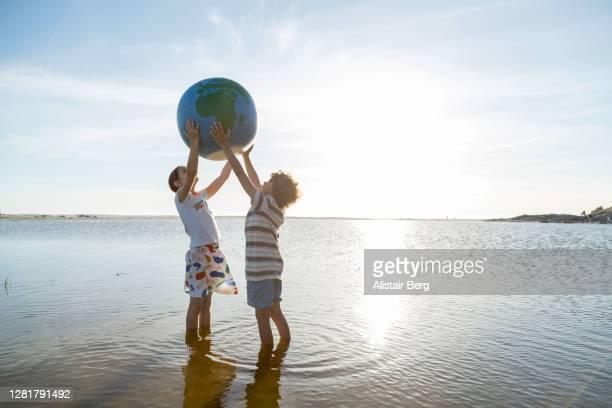 two children holding up a large globe in a lagoon - verantwortung stock-fotos und bilder