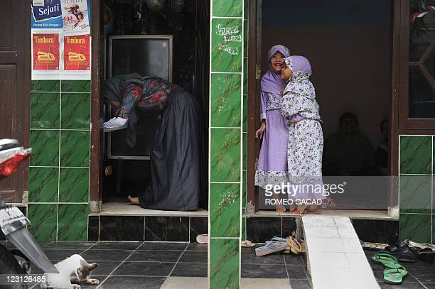 Two children hug each other during a visit to their grandfathers house to celebrate EidalFitr in Jakarta on August 31 2011 The world's most populated...