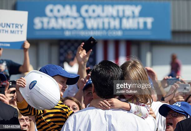 Two children hug Republican presidential candidate former Massachusetts Gov Mitt Romney during a campaign rally on October 5 2012 in Abingdon...