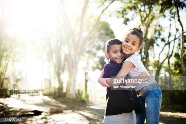 two children hugging each other - family with two children stock pictures, royalty-free photos & images