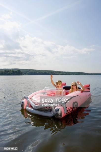 two children in an inflatable raft on a lake - representar fotografías e imágenes de stock