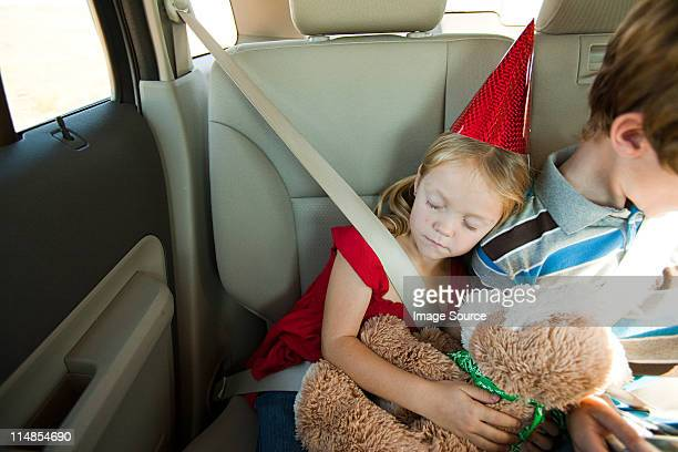 Two children in back seat of car, girl asleep