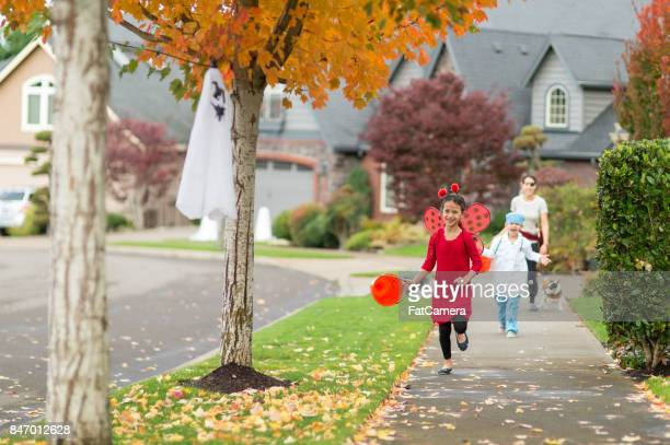 two children in halloween costumes trick or treating - halloween kids stock photos and pictures
