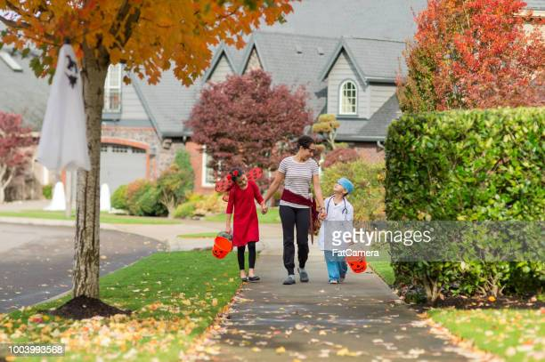 Two children in Halloween costumes trick or treating with their mom