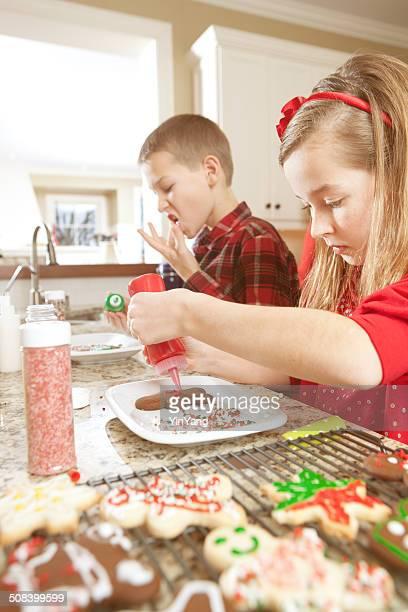 Deux enfants en cuisine glaçage et la décoration de biscuits tout juste sortis du four de Noël