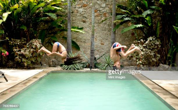 Two children in mid air, somersaulting backwards into a swimming pool.