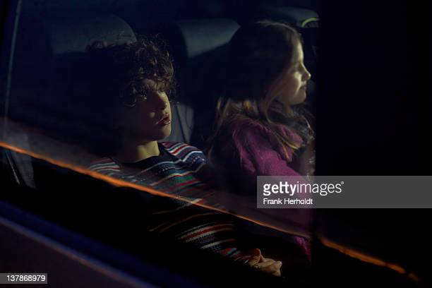 two children in rear seat of car - newpremiumuk stock pictures, royalty-free photos & images