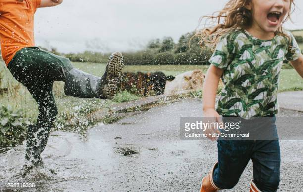 two children in welly boots play in a huge puddle - humour stock pictures, royalty-free photos & images