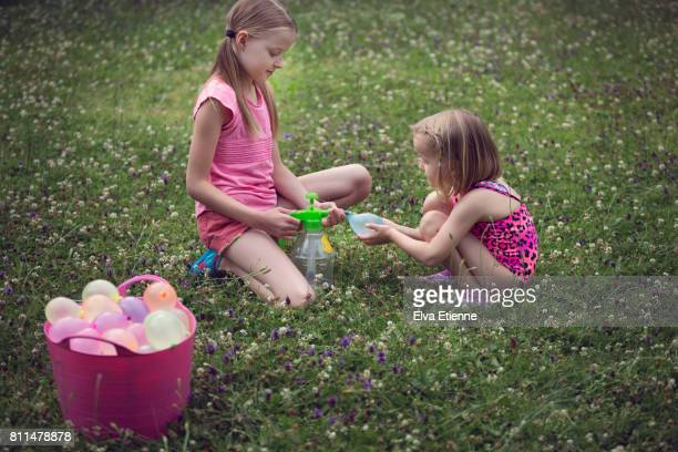 Two children inflating water balloons