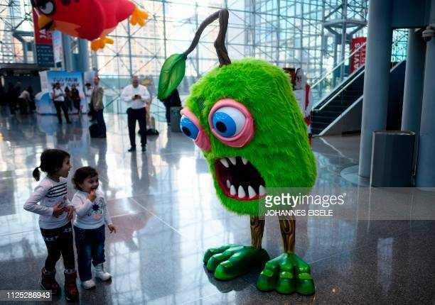 TOPSHOT Two children interact with a giant doll during the annual New York Toy Fair at the Jacob K Javits Convention Center on February 16 2019 in...