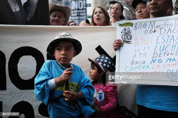 Two children join their parents and hundreds of immigration advocates and supporters at a rally and march to Trump Tower in support of the Deferred...