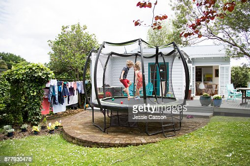 Two children jump on a trampoline in the garden in front of their house