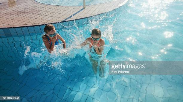 two children jumping into a swimming pool - 鼻をつまむ ストックフォトと画像
