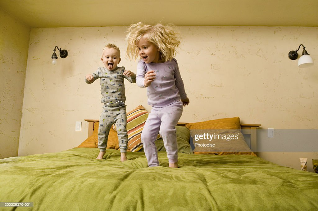 Two children (3-4), (4-5), jumping on bed : Stock Photo