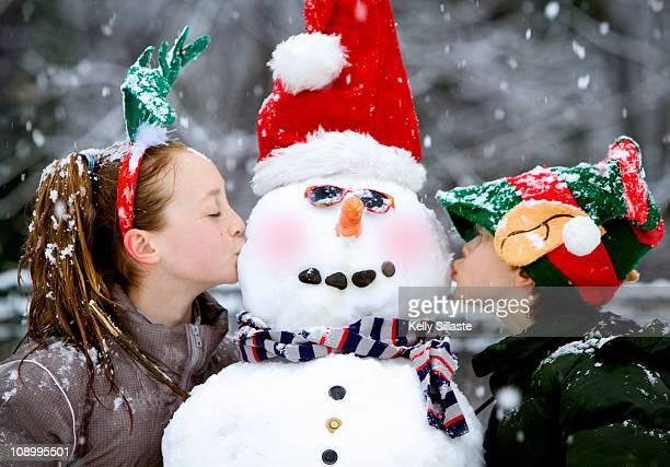 two children kissing a blushing snowman - ピンクの頬 ストックフォトと画像