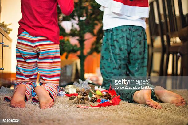 Two children kneeling in from of the Christmas tree putting Christmas decorations.
