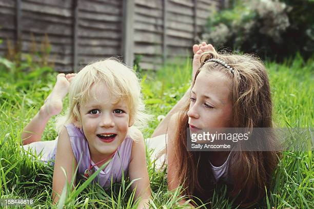 Two children laying on grass outdoors