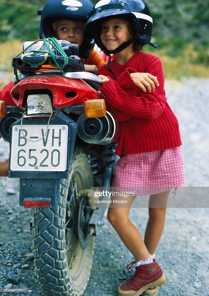 Two children leaning against motorbike : Stockfoto
