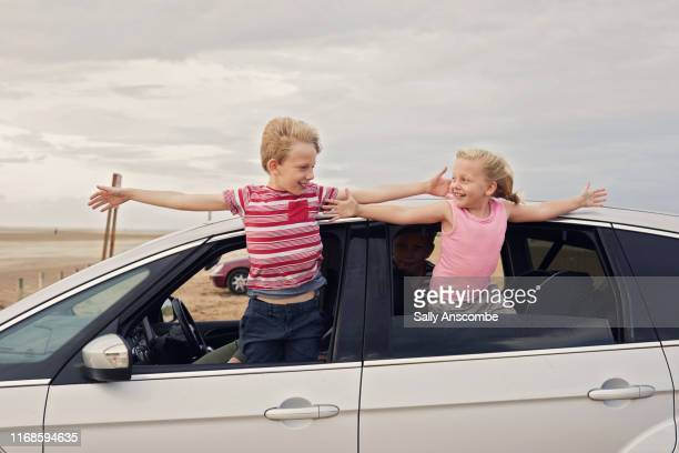 two children leaning out of the car window - southport england stock pictures, royalty-free photos & images