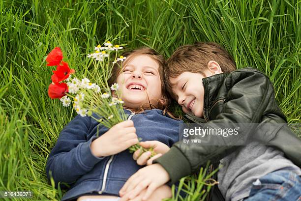 two children lie on the grass