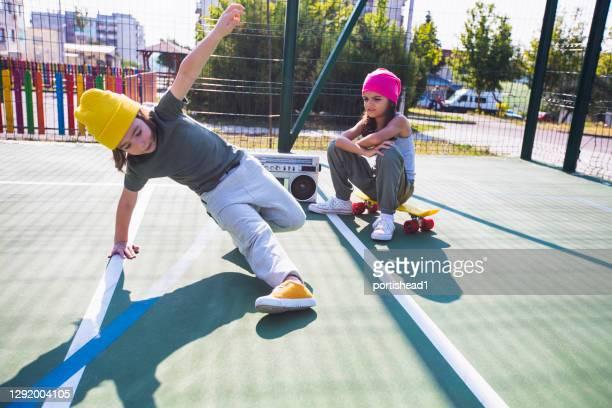 twee kinderen die muziek luisteren, plezier hebben en dansen op een speelplaats - combat sport stockfoto's en -beelden