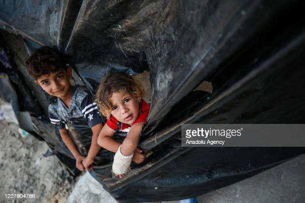 Two children living under difficult circumstances with their family are seen in Rafah Gaza on July 27 2020 Many families living in Gaza strip face...