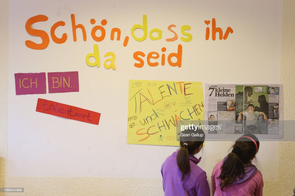 Two children look at a pin-up wall with a headline that reads: 'It's nice that you're here' at the 'Arche' youth center in Marzahn-Hellersdorf district on October 5, 2012 in Berlin, Germany. The Arche (which means Ark) is a Christian-based facility that provides children of all ages with a hot lunch, help with homework, arts and play facilities and in general a welcome place to come to in Marzahn-Hellersdorf district in east Berlin, a district with high levels of unemployment and social problems. An employee said up to 90% of the children come from challenged families and that many arrive at Arche illiterate.
