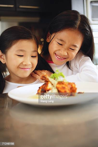 Two children looking at a plate of food, smiling