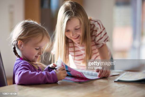two children looking through toy catalogues for gift ideas - nur kinder stock-fotos und bilder