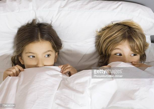 Two children lying in bed with cover pulled up to noses