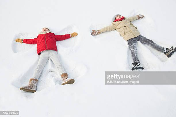 two children making snow angels - snow angel stock photos and pictures