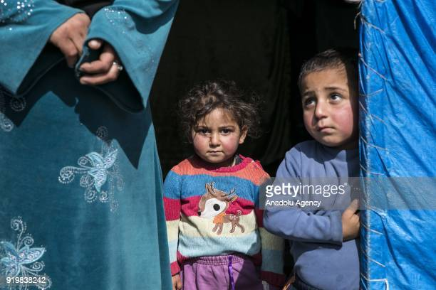 Two children of a family fled from Jinderes district in Syria and sheltered in Reyhanli look out of a tent in Hatay Turkey on February 18 2018 Total...