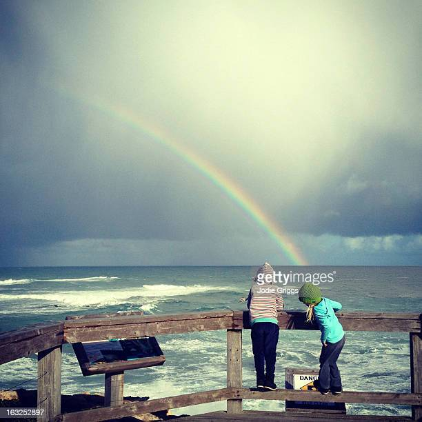 Two children on deck looking at rainbow over ocean