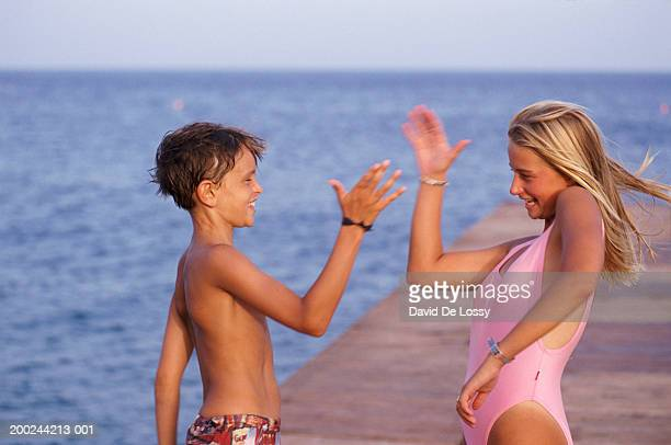 Two children on jetty giving high fives